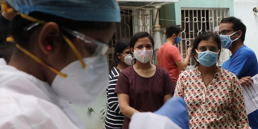 People watch as health workers take swab sample to test for COVID-19 outside a residential building in Mumbai.