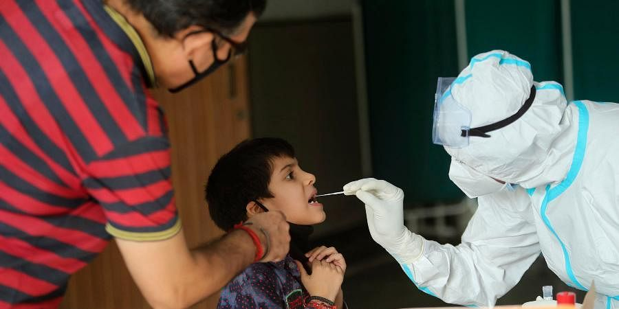 A health worker collects a swab sample to test for COVID-19 at a government hospital in Jammu.