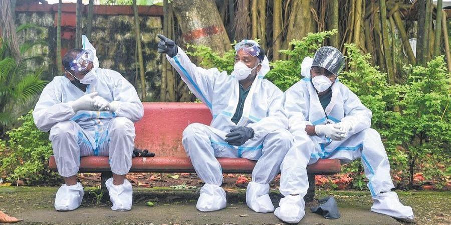 Belagavi corporation workers take a break while on funeral duty on Wednesday | ashishkrishna hp