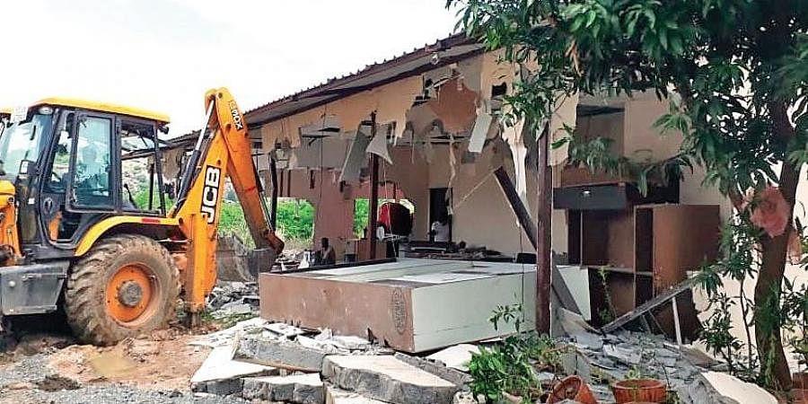 GWMC workers demolish the camp office, built by TRS Wardhannapet MLA Aroori Ramesh on a stormwater drain in Hanamkonda, on Wednesday