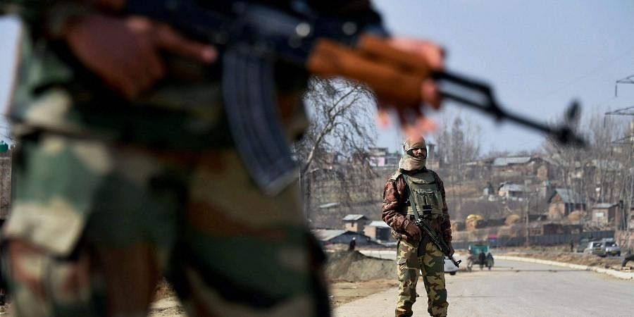 Soliders stand guard on the Srinagar-Jammu National Highway at Awantipora in Pulwama District on Thursday.