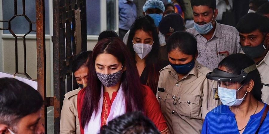 Police personnel take actors Ragini Dwivedi and Sanjjanaa Galrani out of court, after their hearing, in Bengaluru