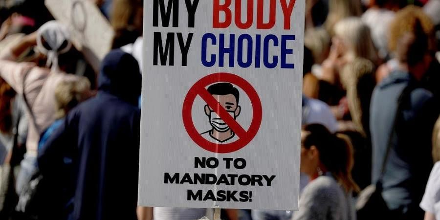 A protester holds up a placard as they take part in a 'Resist and Act for Freedom' protest against a mandatory coronavirus vaccine.