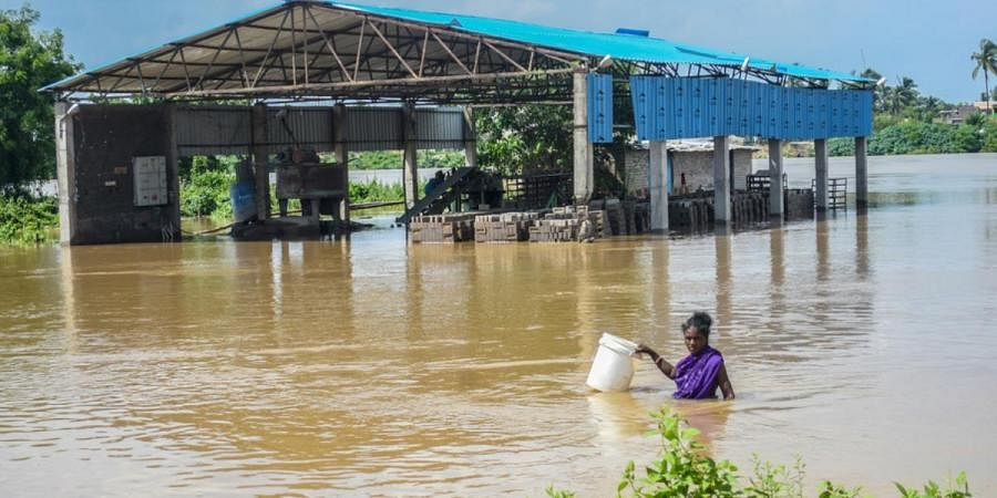 A woman carries a plastic bucket while crossing flood water of Daya river in Bhubaneswar on Tuesday