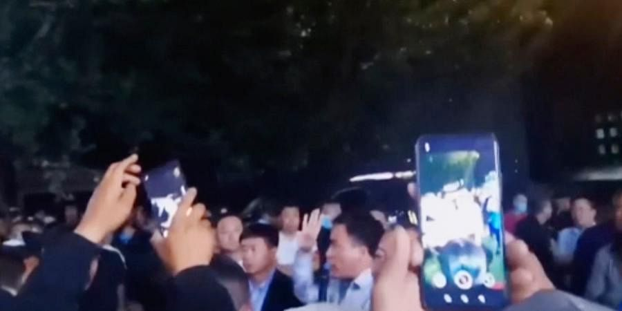 In this image made from video footage by Nure Zhang, parents confront authorities outside a school in Tongliao in Northwestern China's Inner Mongolia region.