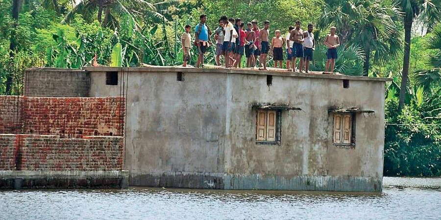 Flood-hit villagers take shelter on the roof of a building in Kendrapara district