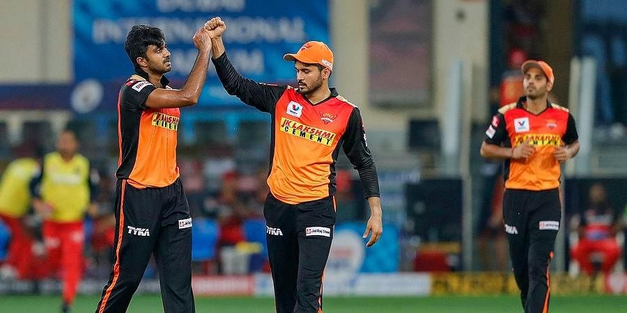 Sunrisers Hyderabad players Manish Pandey and Vijay Shankar celebrate the wicket of Royal Challengers Bangalore batsman Devdutt Padikkal during a cricket match of IPL 2020, at Dubai International Cricket Stadium, Dubai, United Arab Emir