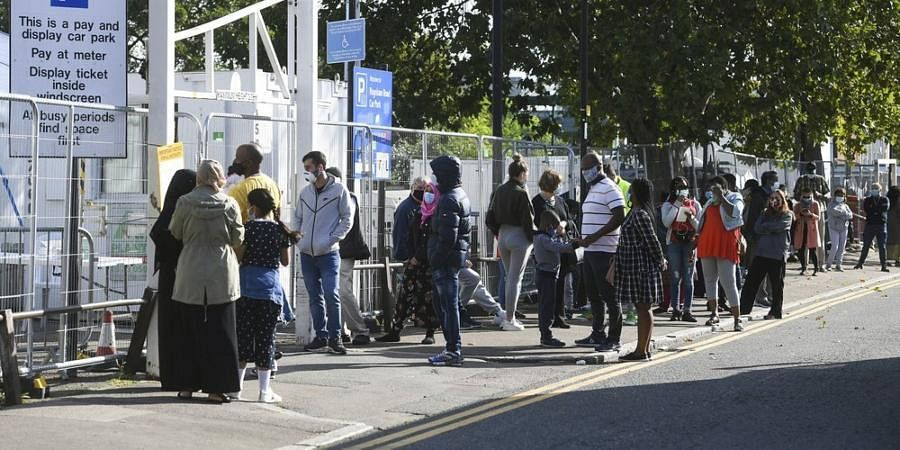 People queue up outside a coronavirus testing centre offering walk-in appointments in north London.
