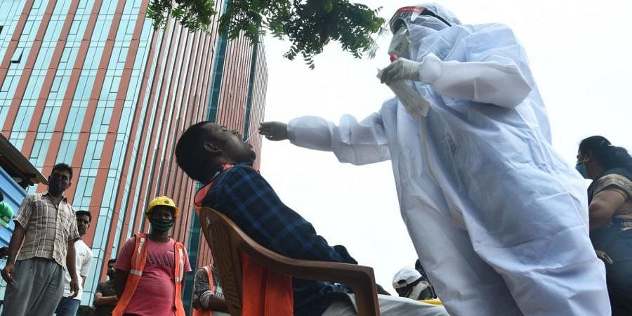 Chennai corporation collect SWAB samples from the migrant workers who are working at the construction site at OMR on Wednesday. (Photo | Ashwin Prasath, EPS)
