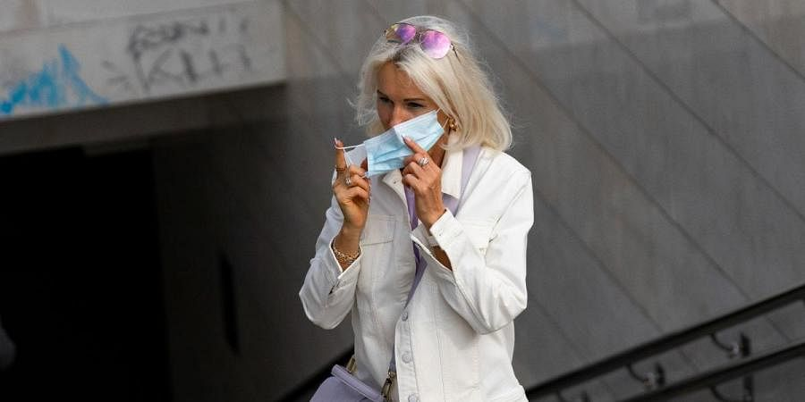 A woman puts on a face mask against coronavirus as she leaves a subway in the center of Moscow