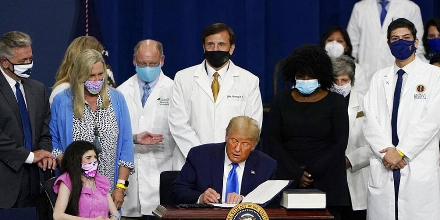 President Donald Trump signs an executive order after delivering remarks on healthcare at Charlotte Douglas International Airport