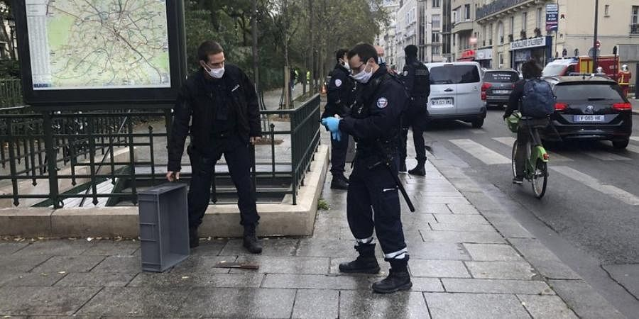 Police officers stand by a knife, seen on the ground, in Paris, Friday, September 25, 2020.