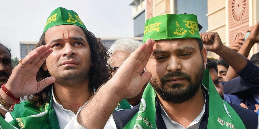RJD leaders Tejashwi Yadav (front) and Tej Pratap wearing party caps during the open session of Rashtriya Janata Dal at Bapu Sabhagar in Patna Tuesday Dec. 10 2019. (Photo | PTI)