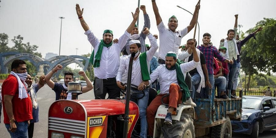 Farmers shout slogans as they ride tractors towards New Delhi to protests against newly passed Farm Laws.