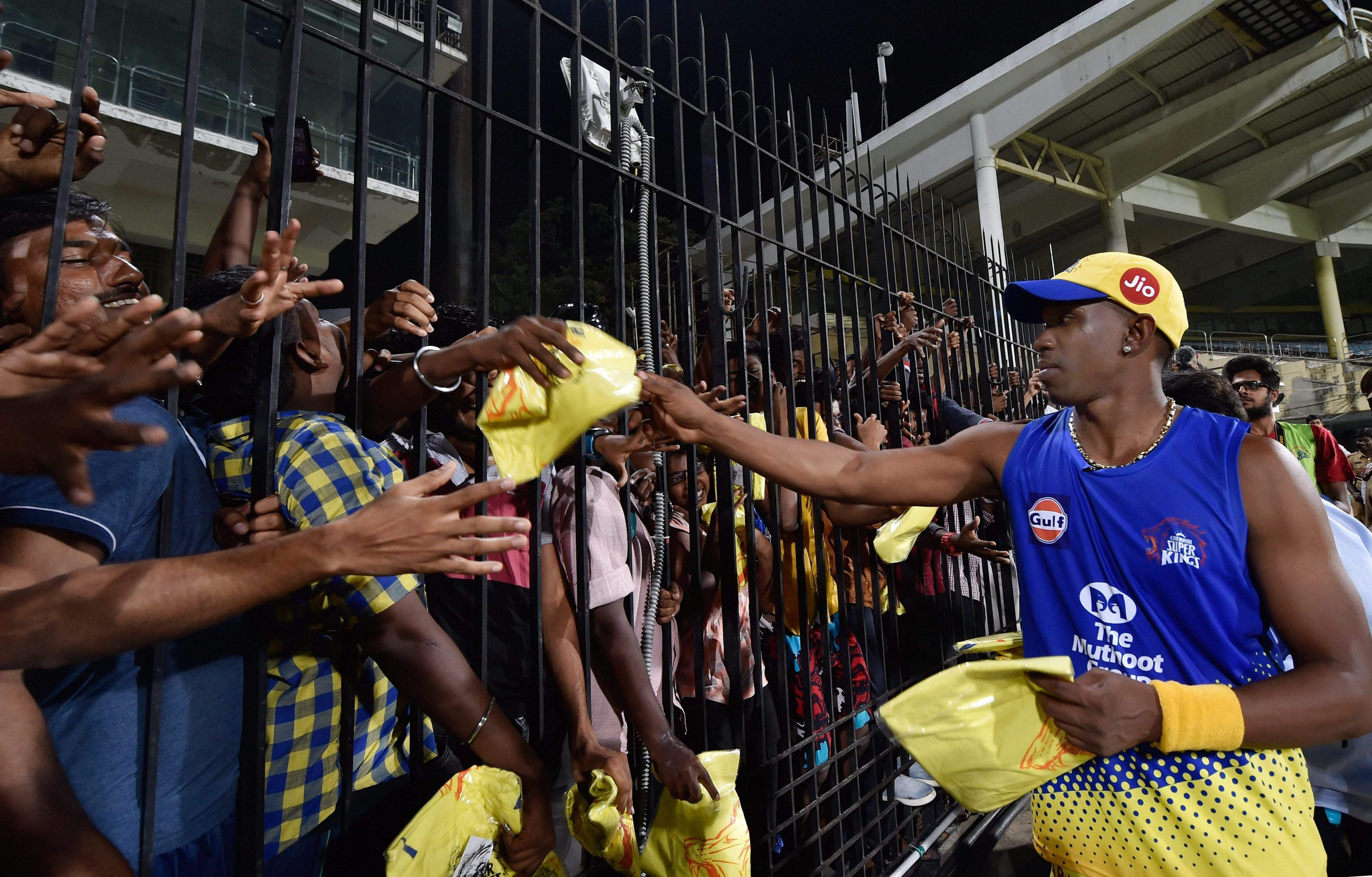 Yellow brigade: The self-styled moniker for CSK fans. This year, however, they, like fans of the other seven teams, will be absent from the three stadia. In picture, CSK player Bravo distributing T-shirts to fans during a practice session of IPL T20-2018 tournament at the Chepauk (File | PTI)