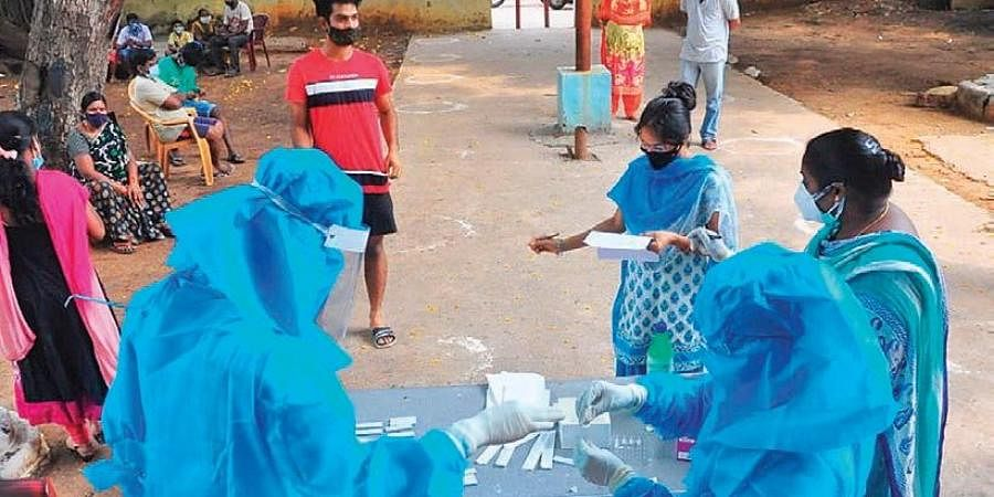 Health workers collect swab samples from people for Covid-19 test in Visakhapatnam on Tuesday. (Photo | G Satyanarayana, EPS)