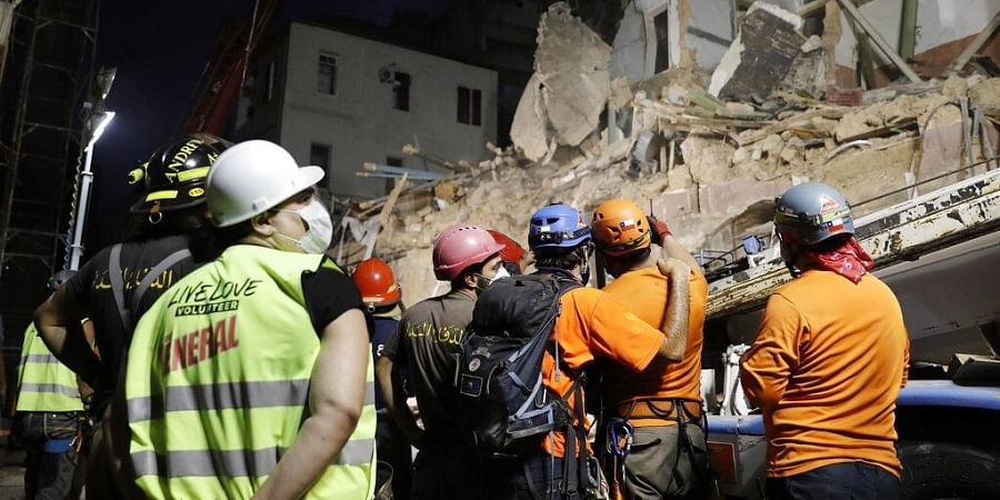 Lebanese and Chilean rescuers watching a crane at the site of a collapsed building after getting signals there may be a survivor buried in the rubble.