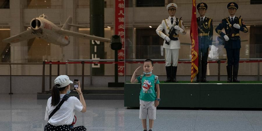 A child salutes for a photo near statues of Chinese military honor guards at the military museum in Beijing.