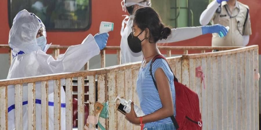 A passenger undergoes thermal screening after arriving from New Delhi by Rajdhani Express at Ranchi Railway Station during the COVID-19 nationwide lockdown