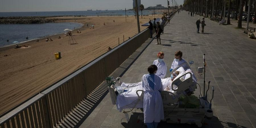 Francisco España, 60, is surrounded by members of his medical team as he looks at the Mediterranean sea from a promenade next to the 'Hospital del Mar' in Barcelona, Spain.