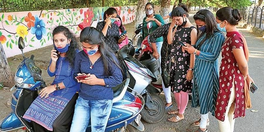 Students browsing mobile phones for their results in Bhubaneswar.