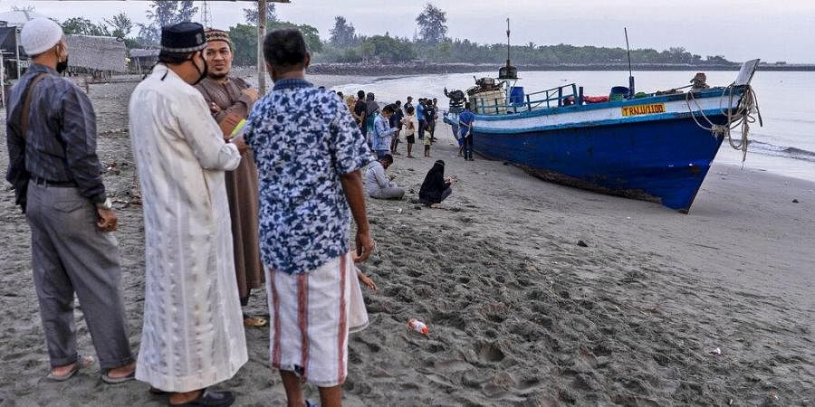 Local residents inspect the boat carrying hundreds of ethnic Rohingya people that landed on a beach in Lhokseumawe, Aceh province, Indonesia, Monday, Sept. 7, 2020. (Photo | AP)