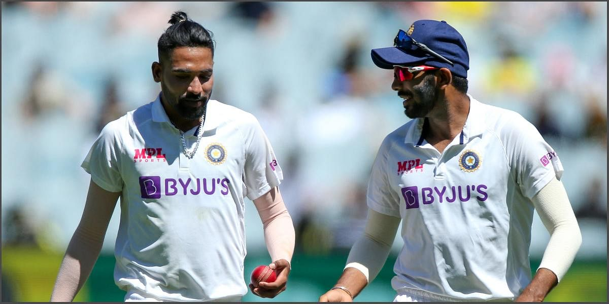 India's Mohammed Siraj (L) and Jasprit Bumrah chat day 1 of the Boxing Day Test match against Australia at the Melbourne Cricket Ground