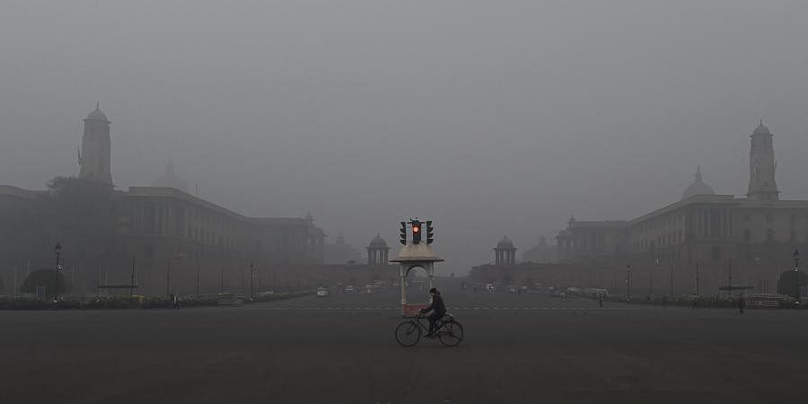 A man rides cycle near the Vijay Chowk amid a cold and foggy winter morning in New Delhi Tuesday