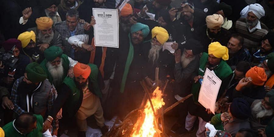 Farmer leaders burn the copies of three farm law during lohri celebrations at Singhu border. (Photo  EPS/ Parveen negi)