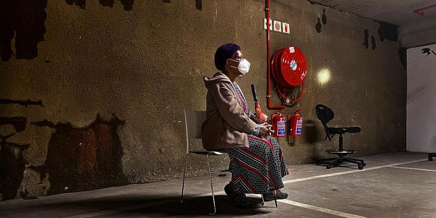 A lone woman waits to be tested for COVID-19 in the parking garage of a shopping mall in Johannesburg