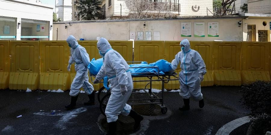 Medical workers move a person who died from COVID-19 at a hospital in Wuhan