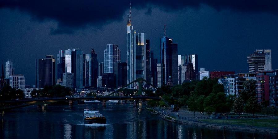 A cargo ship passes on the river Main with the buildings of the banking district in background in Frankfurt