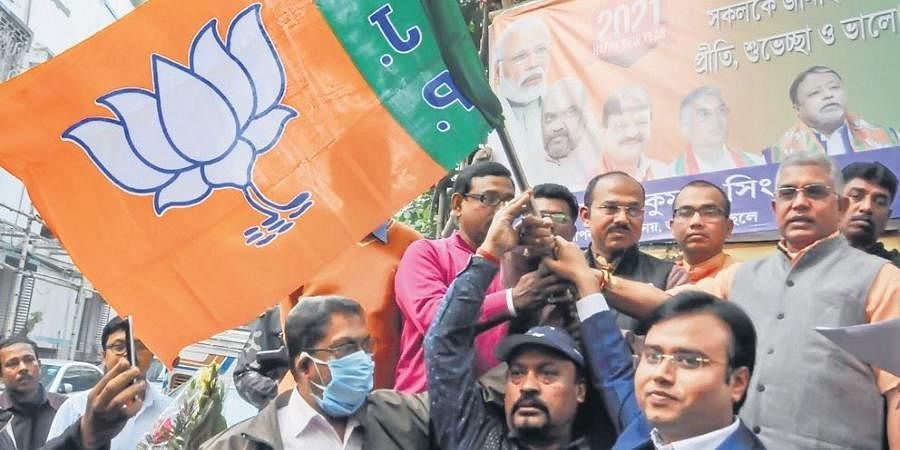 West Bengal BJP president Dilip Ghosh (R) hands over the party flag to a group of lawyers after they joined the saffron party in Kolkata on Saturday.