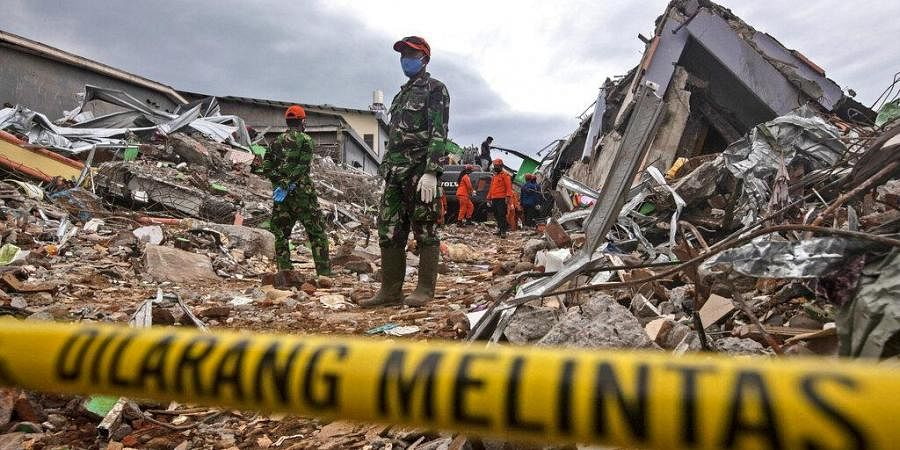Rescuers search for victims at the ruin of a building flattened during an earthquake in Mamuju, West Sulawesi, Indonesia, Saturday, Jan. 16, 2021. (Photo | AP)