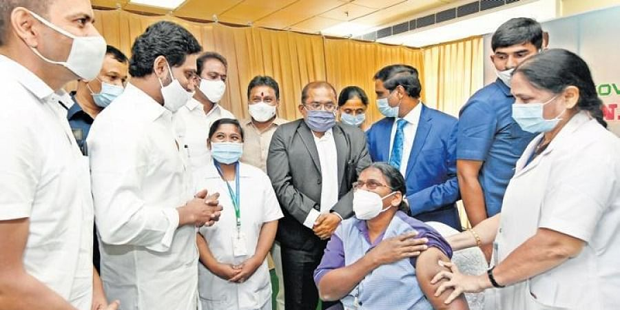 Andhra Pradesh CM YS Jagan Mohan Reddy interacts with B Pushpa Kumari, the firsthealth worker to get the Covid vaccine, at the GGH in Vijayawada. (Photo | EPS)