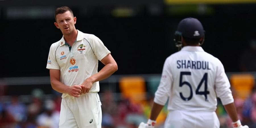 Australia's Josh Hazlewood (L) shares at India's batsman Shardul Thakur (R) on day three of the fourth cricket Test match. (Photo   AFP)