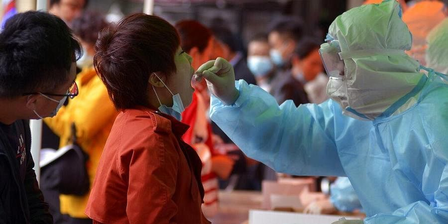 A medical staff takes a swab from a woman as residents line up for the COVID-19 test near the residential area in Qingdao in east China's Shandong province.