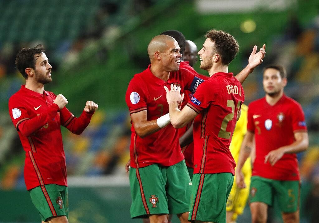 Portugal's Diogo Jota, second right, celebrates with teammate Pepe after scoring his side's second goal during the UEFA Nations League soccer match between Portugal and Sweden
