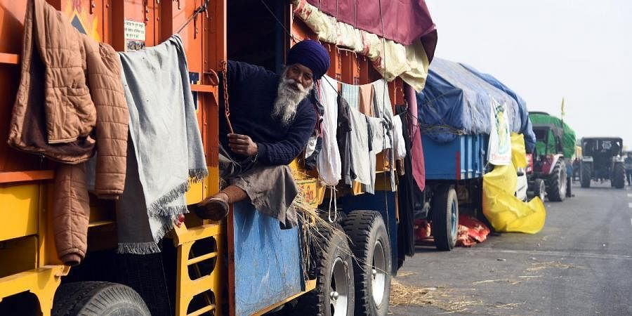 A farmer sitting inside a parked truck at Ghaziabad border on a chilling afternoon