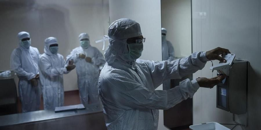 Employees prepare themselves before getting inside a lab where Covishield, AstraZeneca-Oxford's Covid-19 coronavirus vaccine is being manufactured, at India's Serum Institute.