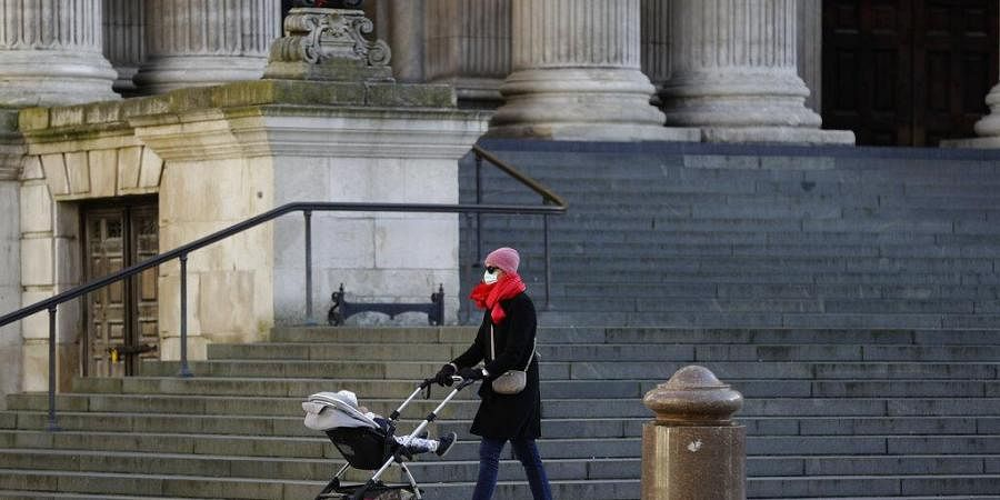 A woman wearing a face mask to curb the spread of coronavirus pushes a child in a buggy past the steps of St. Paul's Cathedral, in the City of London financial district of London.