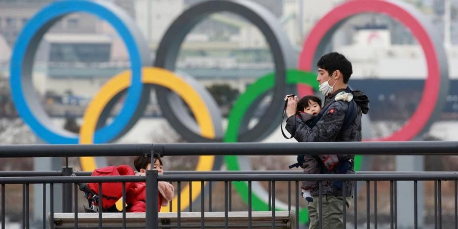 People wearing face masks to protect against the spread of the coronavirus stand at the Odaiba waterfront as Olympic rings is seen in the background in Tokyo