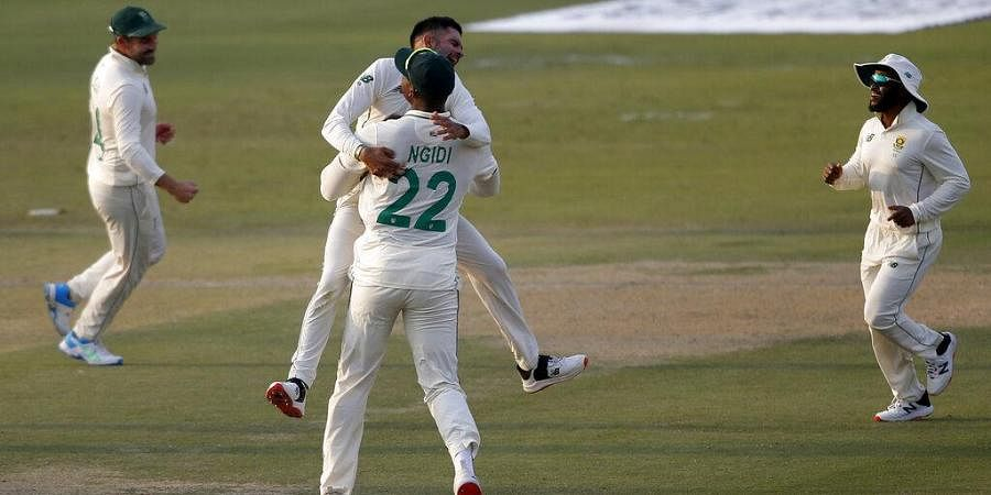 South Africa's spinner Keshav Maharaj, center without cap, celebrates with teammates after the dismissal of Pakistan's Babar Azam during the first day of the first cricket test match.