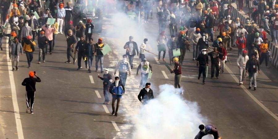 Police use tear gas on protesting farmers during a tractor rally on 72nd Republic Day at Akshardham Ring Road in New Delhi