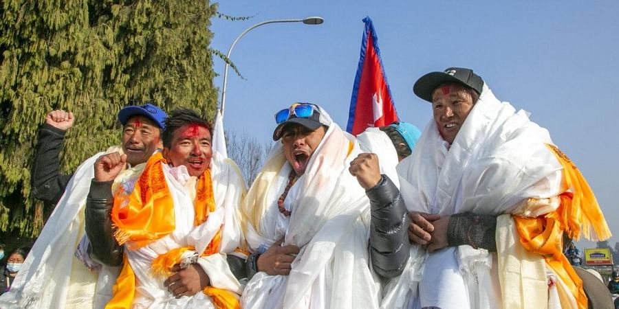 The all-Nepalese mountaineering team that became the first to scale Mount K2 in winter cheer as they arrive at Tribhuwan International airport in Kathmandu, Nepal