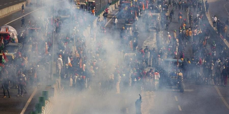 Protesting farmers are seen amid tear gas smoke fired by police in an attempt to stop them from marching to the capital during India's Republic Day celebrations in New Delhi