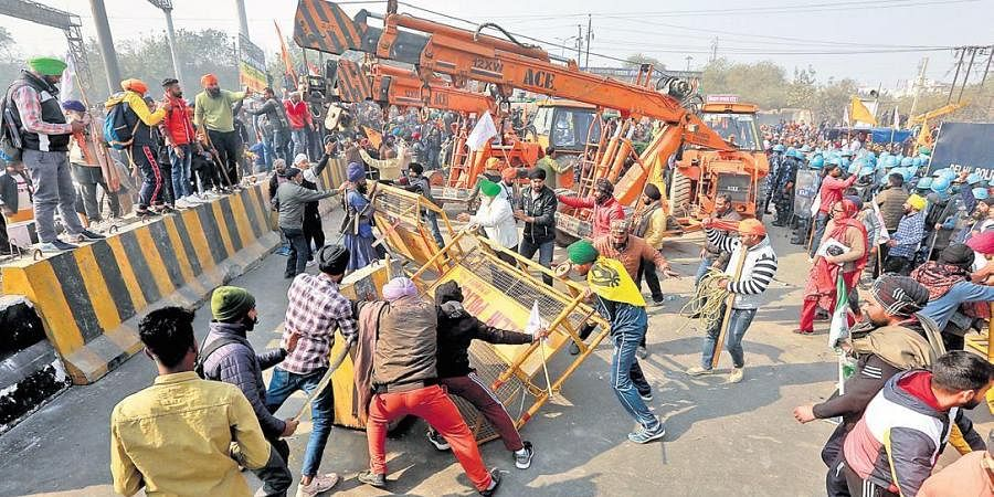 Farmers and their supporters remove barricades during the tractor rally near  Sanjay Gandhi Transport Nagar in New Delhi.