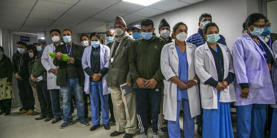 Health workers observe a minute of silence in memory of people who died due to COVID-19 before administering vaccine at Teaching Hospital in Kathmandu, Nepal.