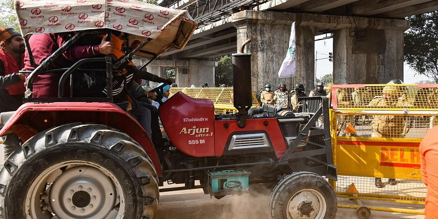 The protesting farmers were stopped at different points by police. In picture, a tractor tries to break a police barricade near Akshardham in New Delhi. (Photo | EPS)