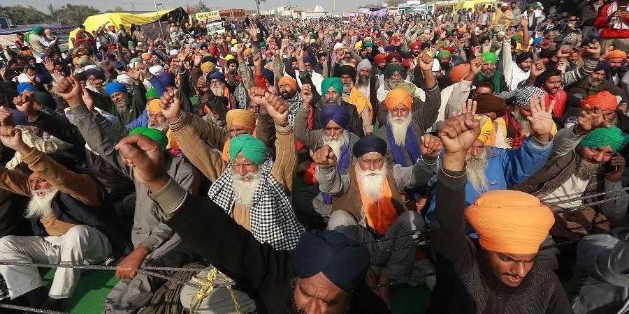 Farmers shout slogans during their protest against the new farm laws.